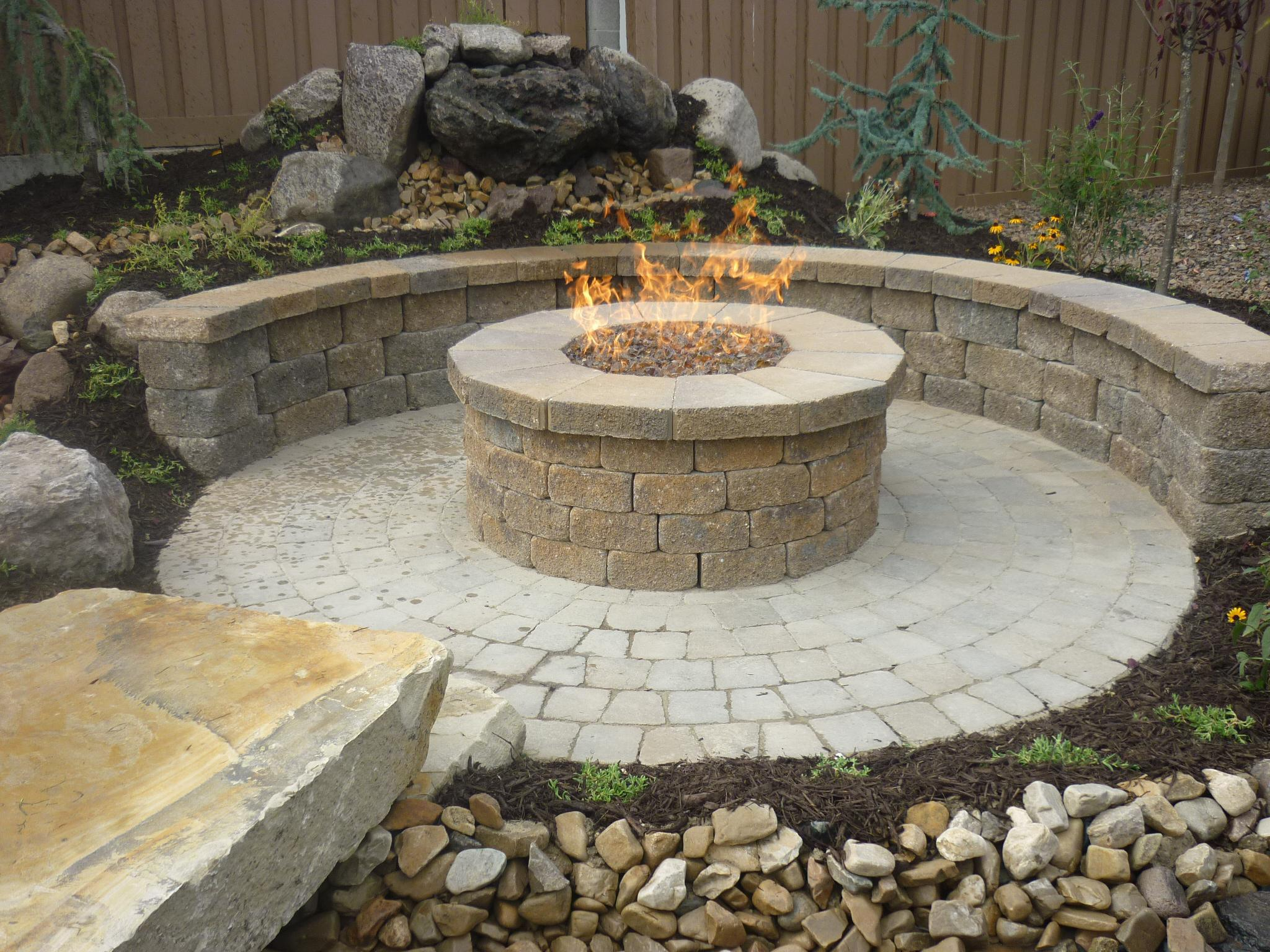 Backyard fire glass landscaping rocks for Garden designs with stone circles